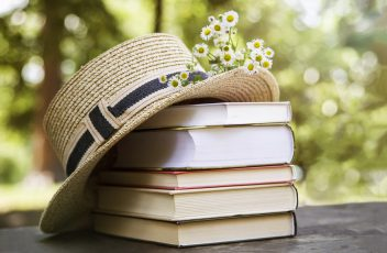 A stack of books on an old wooden table next to a straw hat of a canoe and a bouquet of wild flowers.